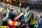 Jamaica's Usain Bolt reaches out to a young spectator as he celebrates after anchoring the Jamaican team to the gold medal in the Men's 4x100m relay at Hampden Park Stadium. Photo / AP.