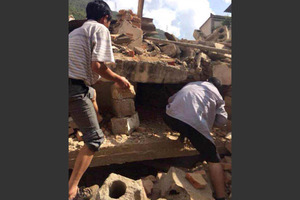 In this photo taken by cellphone and released by China's Xinhua News Agency, men look for survivors after an earthquake in Ludian County. Photo / AP