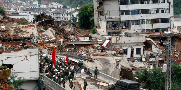 Rescue workers search for survivors amid the remains of collapsed buildings at the epicenter of Sunday's earthquake that struck the town of Longtoushan. Photo / AP