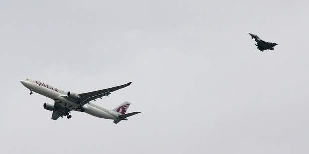 A military fighter jet escorts a passenger jet as it comes in to land at Manchester airport, after a threat was made. Photo / AP