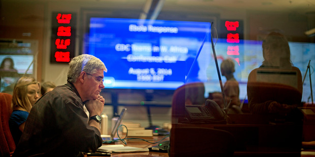 U.S. Centers for Disease Control and Prevention officials sit in on a conference call about Ebola with CDC team members deployed in West Africa. Photo / AP