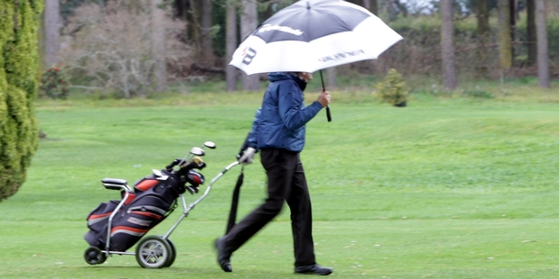 Golfers went under umbrellas at the Napier Golf Course, near Taradale, yesterday. Photo / Paul Taylor