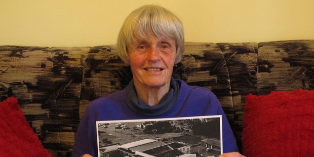 Karen Fletcher with a photo of the Kaikohe Hotel in better times. The aerial picture was taken by the RNZAF in 1968. Photo / Peter de Graaf