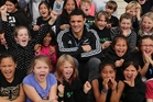 Dan Carter, cracked leg and all, with his young fans at Paihia School. Photo / John Stone