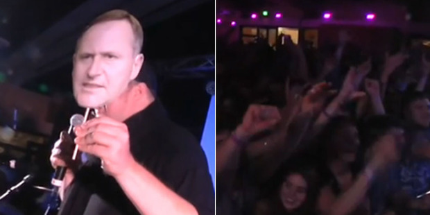 Loading Stills from the video posted by the Internet-Mana party showing the crowd in a frenzy by Dotcom, left, holding a cut-out mask of John Key.