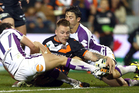 Blake Austin of the Tigers drops the ball over the tryline as Billy Slater and Cooper Cronk defend. Photo / Getty Images
