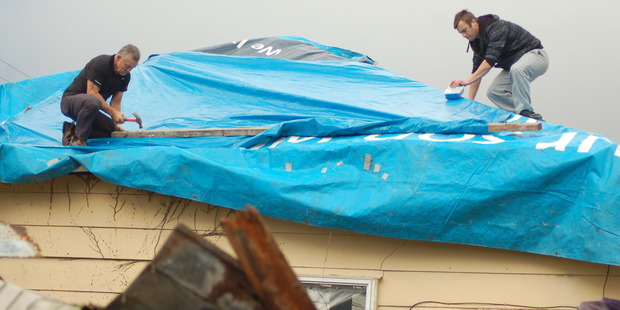 Grey District mayor Tony Kokshoorn (left) chipped in to help repair Marcia Pere's Blaketown home. Photo / Greymouth Star
