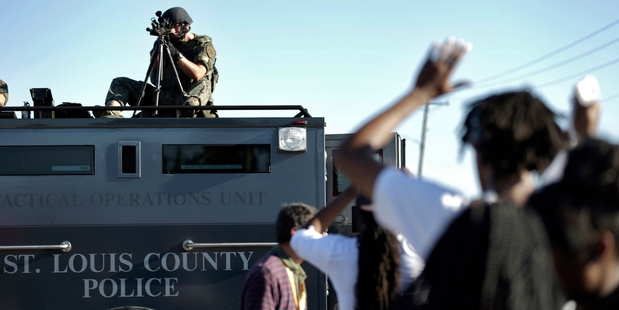 A St Louis County policeman aims his weapon at American protesters in Ferguson, Missouri. Photo / AP