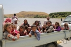 Desperate Yazidis cross the Iraq-Syria border at Feeshkhabour bridge over the Tigris River. Photo / AP