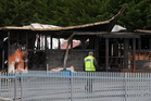 A firefighter walking past the destroyed classrooms at Paraparaumu School. Photo / Mark Mitchell