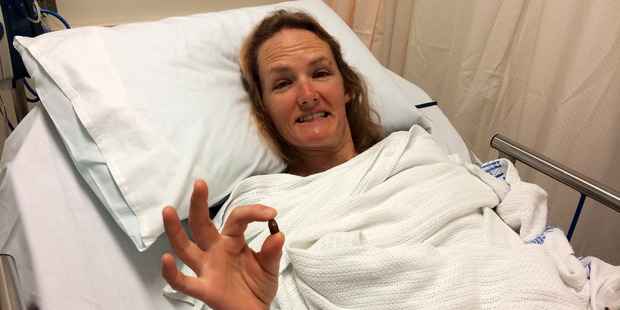 Waihi Beach woman Cathy Franzoi recovering in hospital and holding the bullet that was removed from her leg. Photo / Supplied