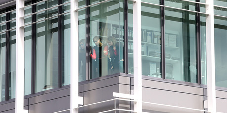 People inside the office peer down at the scene of the fall. Photo / John Borren