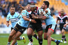 Manu Vatuvei of the Warriors looks to beat the tackle of Andrew Fifita, right, and Tupou Sopoaga of the Sharks. Photo / Simon Watts / Getty Images