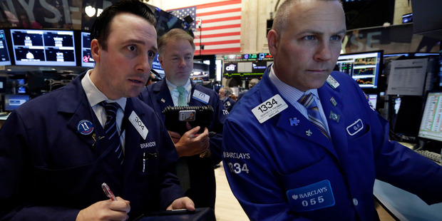 Specialist Geoffrey Friedman, right, works with traders on the floor of the New York Stock Exchange. File photo / AP