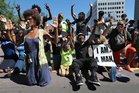 Protestors drop to their knees in a rally for Michael Brown Jr, who was shot and killed by a Ferguson cop. Photo / AP