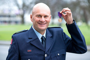 Christchurch fireman Terry Gyde holds his New Zealand Bravery Award at the Transitional Cathedral. Photo / Martin Hunter