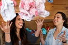 Whangarei sisters Latoya Hood, 19 and Kasey Hood, 16, with some of the baby clothes they have had donated to their Pepi Pride campaign. Photo / Tania Newman
