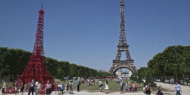 People stroll in front of a replica of the Eiffel Tower, build out of bistro chairs. Photo / AP
