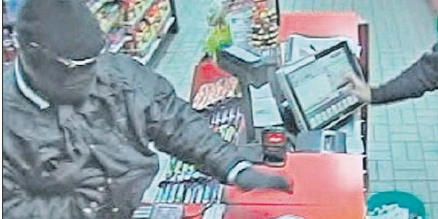 SEEN EARLIER: The closed-circuit footage from Mobil Mart in Taradale Rd shows the robber appearing to be going for a weapon hidden in his top.