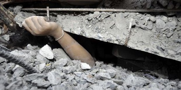 A trapped worker calls for help from the rubble. Photo / AP