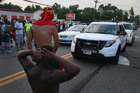 Demonstrators protesting the shooting death of Michael Brown block the path of police vehicles in Ferguson, Missouri. Photo / Getty