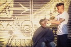 Hair stylist Mark Bustos cuts the hair of a homeless person. Photo / Devin Masga
