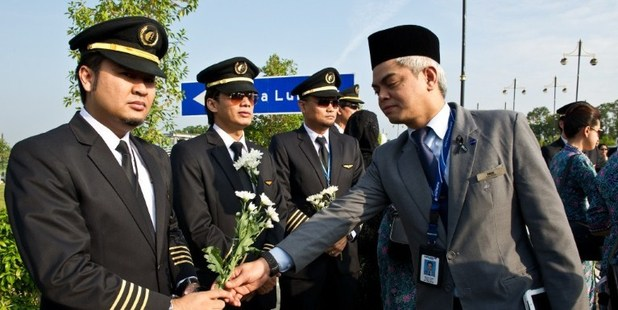 A man gives white flowers to a Malaysia Airlines pilot before the arrival of the Malaysian remains who perished aboard flight MH17. Photo / AFP