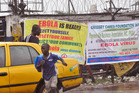 People pass by Ebola virus health warning signs, in the city of Monrovia, Liberia. Photo / AP