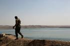 A Kurdish peshmerga fighter patrols near the Mosul Dam at the town of Chamibarakat outside Mosul, Iraq. Photo / AP