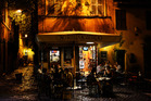 Tourists and locals gather at Trastevere's popular restaurants after dark.