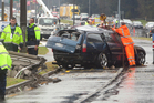 Police are seeking witnesses to this crash which happened in the middle of torrential rain on Wednesday morning. It left a teenager seriously injured and brought down power poles on nearby cars. Photo / Ben Fraser