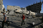 Palestinians walk by the rubble of the toppled minaret of the Abu Jihad Al Wazer mosque, destroyed by an Israeli strike during the war, in Gaza City. Photo / AP