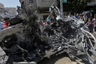 Palestinians inspect the wreckage of a vehicle after an Israeli airstrike at the main street in Gaza City. Photo / AP
