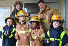 Four young Springbank School pupils won a ride on a fire engine, and a chance to dress up in firefighting uniforms, after entering a colouring competition raising money for the Blood and Leukemia Foundation. The winners, from left, were Millie Stovell (6), Heidi Traas (7), Dexter Badger (6) and Daniel Sutcliffe (6). With them are firefighters Charlotte Stanley-Scott and Tony Scott.