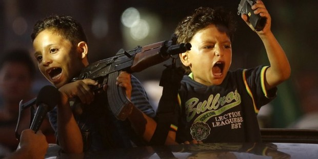 Children hold up guns (one with an empty magazine) from a car as Palestinians gather in the streets to celebrate a ceasefire which ends 50 days of conflict. Photo / AFP