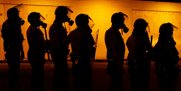 Police wait to advance after tear gas was used to disperse a crowd during a protest for Michael Brown. Photo / AP