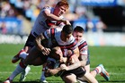 Sam Tomkins of the Warriors is tackled by Sonny Bill Williams and Shaun Kenny-Dowall of the Roosters. Photo / Getty.