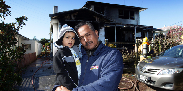 Mohammed Sattar and grandson Mohammed Ariz who live at the property affected by the blaze in Kelston. Photo / Herald on Sunday / Doug Sherring