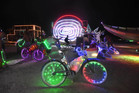 A Burning Man participant's bike is surrounded by art cars that are lined up at the Black Rock DMV to be registered at Burning Man. Photo / AP