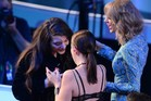 Lorde arrives to accept the trophy for Best Rock Video for Royals on stage from Taylor Swift, right, at the MTV Video Music Awards. Photo / AFP