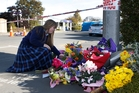 Sarah McCrea, a friend of Lindy Curtis' daughter, places flowers across the street from the office where the three women were shot. Picture / Mark Mitchell