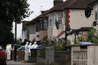 Police forensics personnel examine the scene on a street in Edmonton, north London, after a woman was found dead following a beheading. Photo / AFP