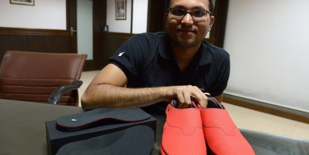 LeChal co-founder Krispian Lawrence with a pair of the red smart sneakers. Photo / AFP