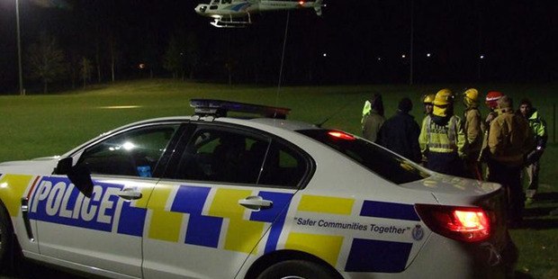 Emergency services staff watch a rescue helicopter land on Anderson Park in Cromwell last night after its return from a fire at Northburn Station. Photo / Lynda Van Kempen.