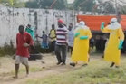 The man in red can be seen wearing a white tag - showing he has tested positive for Ebola. Photo / still from video