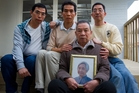 Ri Dong Liu holds a picture of Jie Rong Luo. Behind him are sons, from left, Guo Xiong Liu, Chi Hong Lao and Sui Xiong Liu. Photo / Jason Oxenham