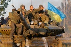 Soldiers of Ukrainian army ride on a tank in the port city of Mariupol, southeastern Ukraine. Photo / AP
