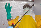 A health worker is sprayed with disinfectant after he worked with patients that contracted the Ebola virus. Photo / AP