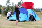 BLUSTERY: Sean George demonstrates the wind strength using his towel while Troy Malofy (left) and Brodie Cleverly bang in a few more tent pegs. PHOTO/MICHAEL CUNNINGHAM