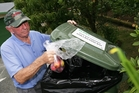 BIOSECURITY MEASURE: Mike Brophy, Red Zone resident and gardener from Tanekaha Drive, puts fruit in a Ministry of Primary Industries collection bin. PHOTO/RON BURGIN
